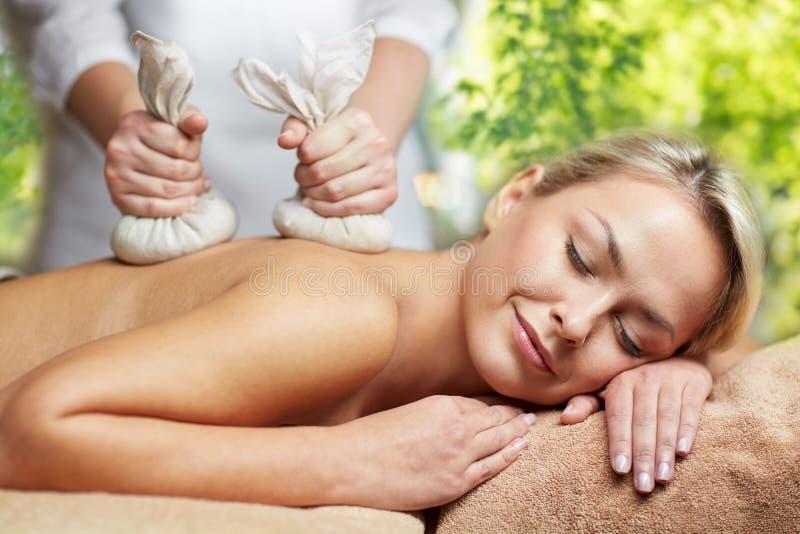 Fermez-vous de la femme ayant le massage de fines herbes de sac dans la station thermale image libre de droits