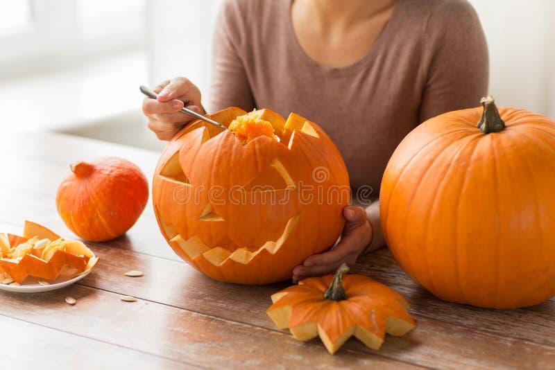 Fermez-vous de la femme découpant le potiron de Halloween photos stock