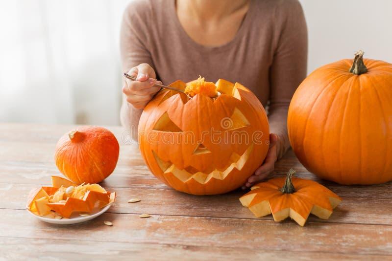 Fermez-vous de la femme découpant le potiron de Halloween photographie stock libre de droits