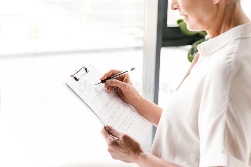 Fermez-vous de la femme d'affaires mûres prenant des notes photo stock