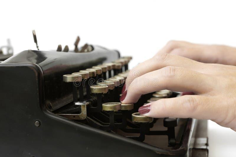 Fermez-vous de la femme dactylographiant avec la vieille machine à écrire photographie stock libre de droits