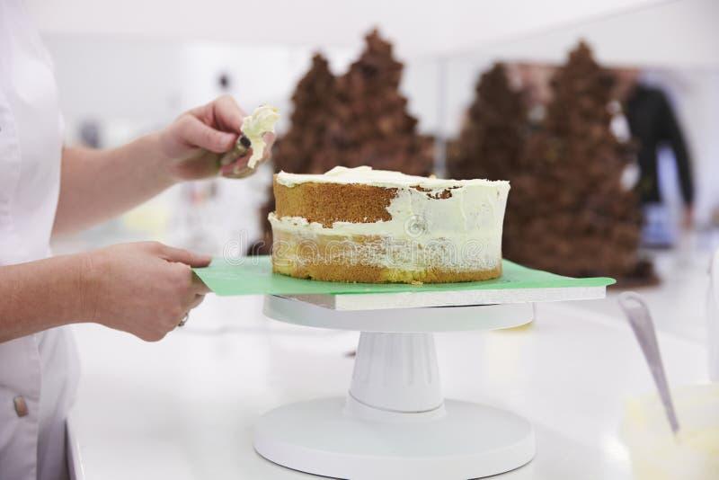 Fermez-vous de la femme dans la boulangerie décorant le gâteau avec le glaçage photographie stock