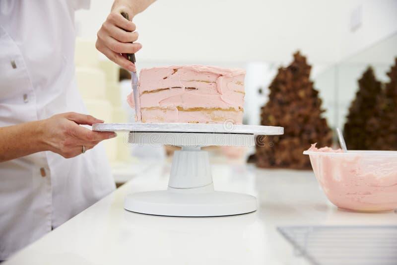 Fermez-vous de la femme dans la boulangerie décorant le gâteau avec le glaçage image libre de droits