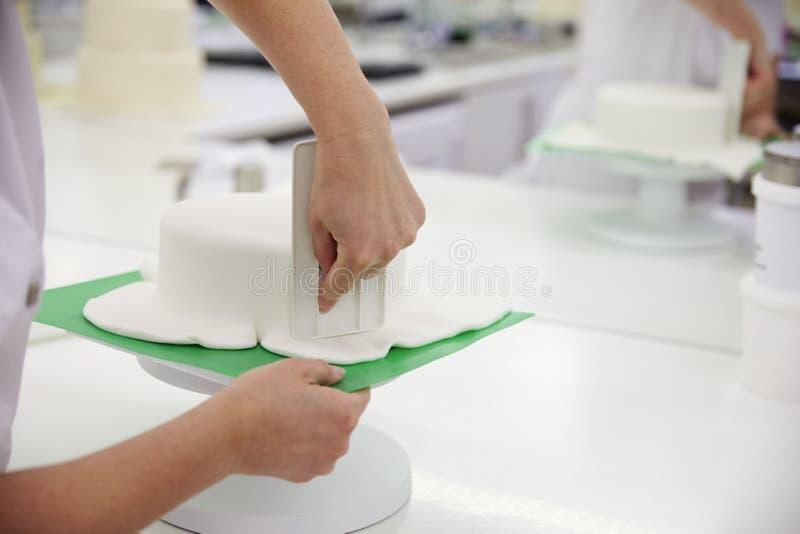 Fermez-vous de la femme dans la boulangerie décorant le gâteau avec le glaçage royal photo libre de droits