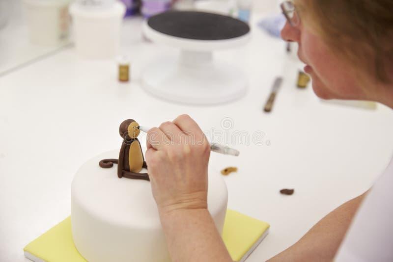 Fermez-vous de la femme dans la boulangerie faisant la décoration de gâteau de singe image libre de droits