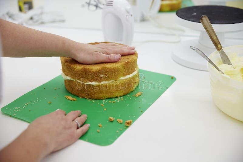 Fermez-vous de la femme dans la boulangerie préparant le gâteau pour la décoration images stock
