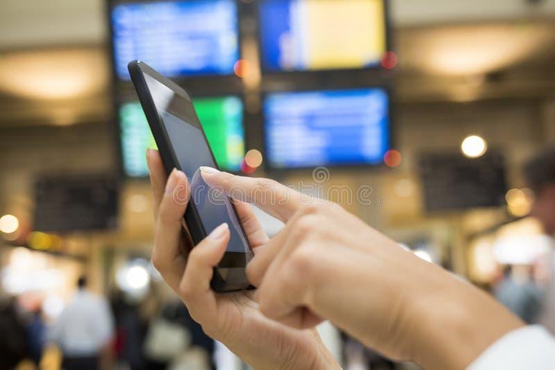 Fermez-vous de la femme de mains à l'aide de son téléphone portable dans la station, backgro photo libre de droits
