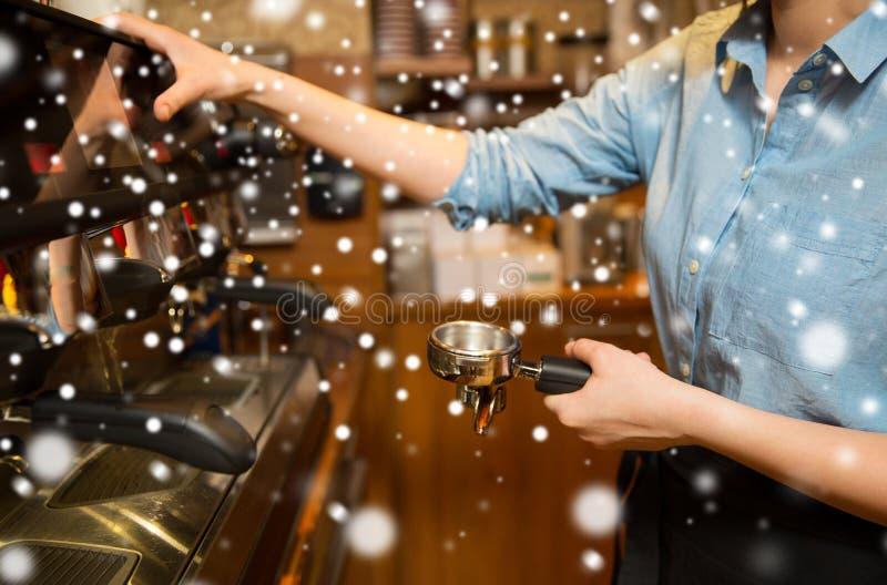 Fermez-vous de la femme faisant le café par la machine au café photographie stock