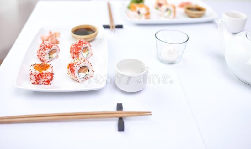 Fermez-vous de la femme mangeant des sushi au restaurant photographie stock
