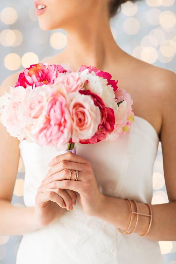 Fermez-vous de la femme ou de la jeune mariée avec le bouquet de fleur image stock