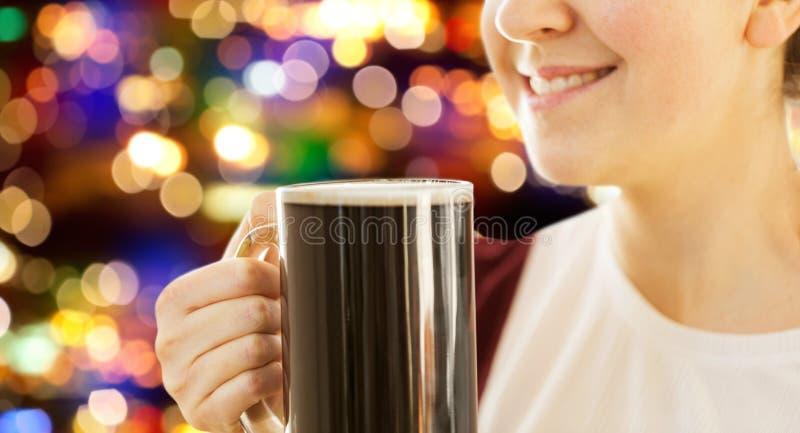 Fermez-vous de la femme de sourire avec de la bière foncée dans la tasse image libre de droits