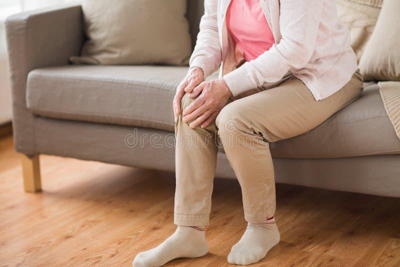 Fermez-vous de la femme supérieure avec douleur dans la jambe à la maison photos stock
