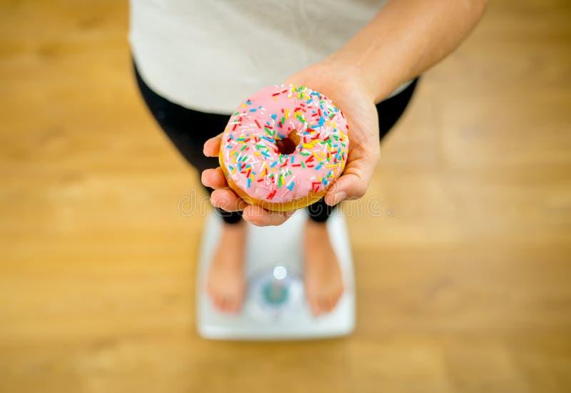 Fermez-vous de la femme sur l'échelle tenant le beignet délicieux dans l'obésité et le concept malsain de nourriture photos stock