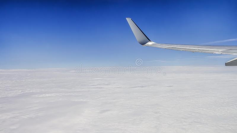Fermez-vous de la fenêtre avec l'aile d'avion Beau cloudscape avec le ciel bleu clair photos libres de droits