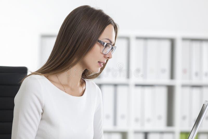 Fermez-vous de la fille dans l'ordinateur portable proche blanc dans le bureau image stock