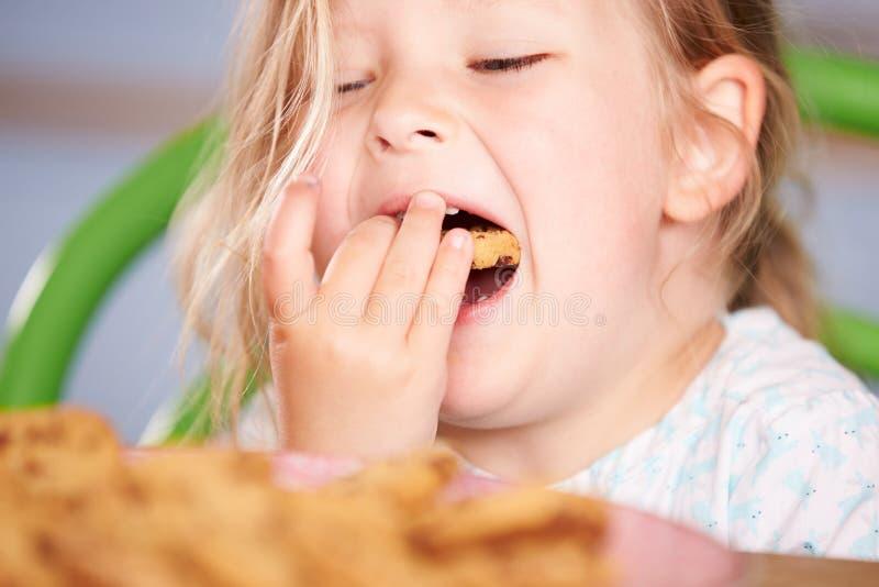 Fermez-vous de la fille mangeant du chocolat Chip Cookie images stock