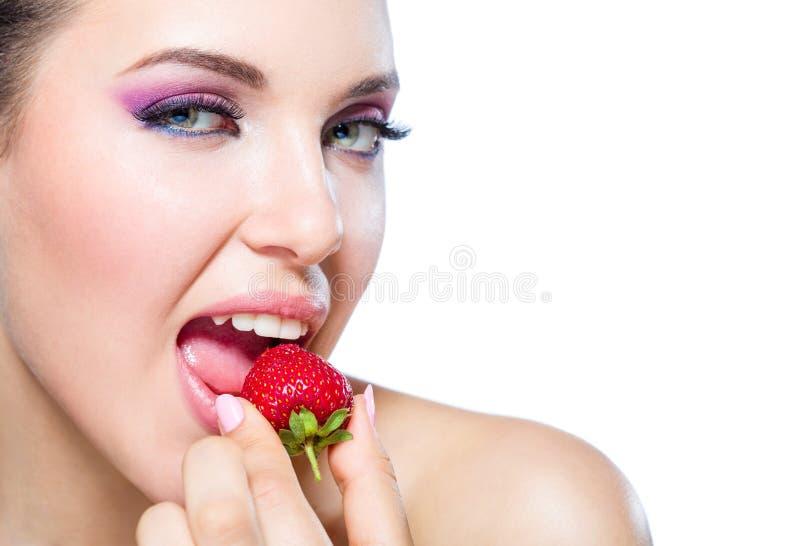 Fermez-vous de la fille mangeant la fraise images libres de droits