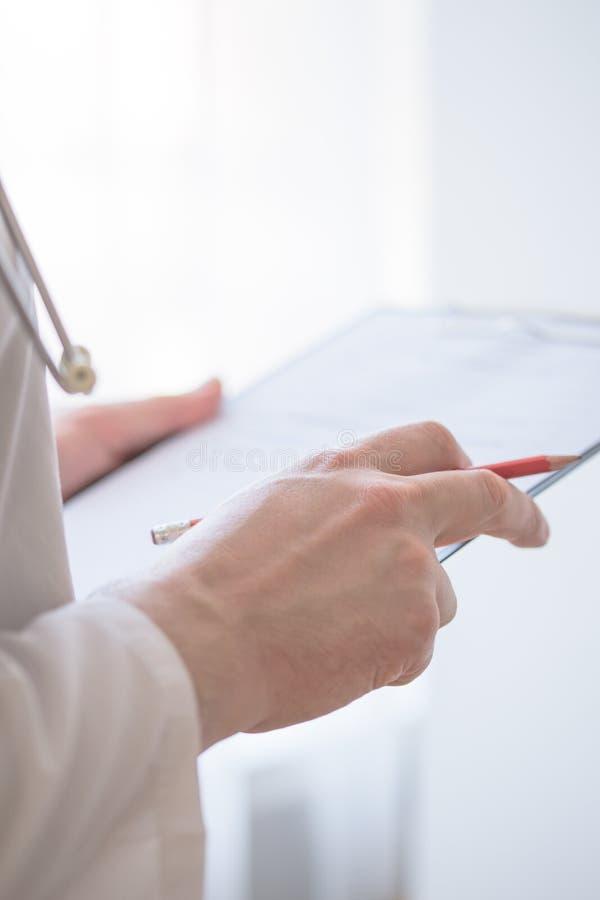 Fermez-vous de la forme masculine de docteur Filling The Medical de main Plan rapproché de la forme masculine de docteur Filling  photographie stock