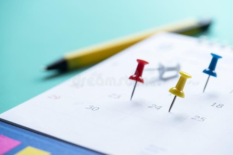 Fermez-vous de la goupille sur le calendrier sur la table photo stock