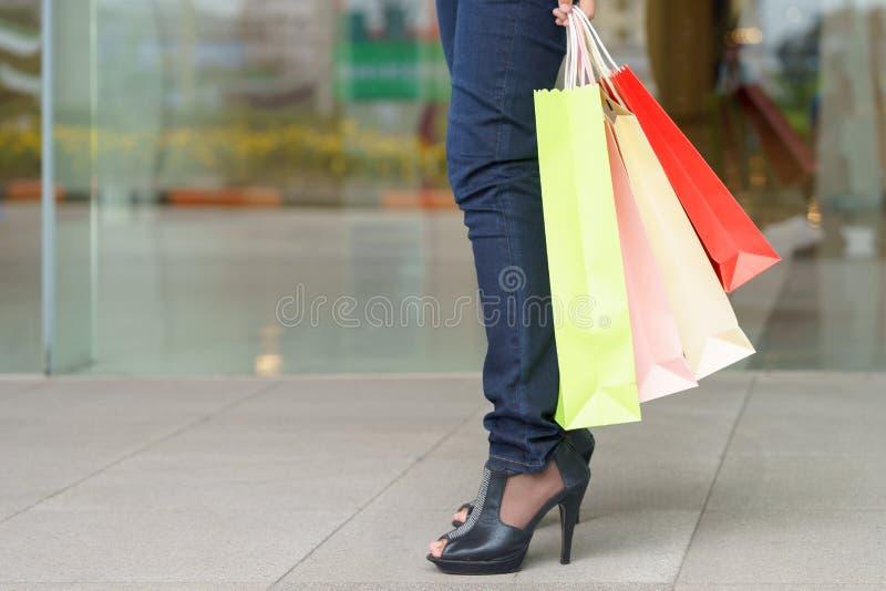 Fermez-vous de la jambe de cliente de femme avec les paniers de papier colorés photos stock