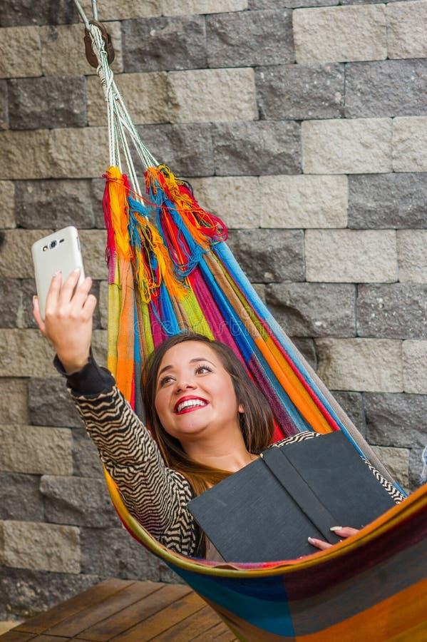 Fermez-vous de la jeune belle femme détendant dans un hamac et prenant un selfie avec son comprimé tandis que tient un livre avec photographie stock libre de droits