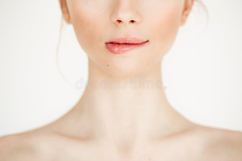 Fermez-vous de la jeune belle fille avec la lèvre acérée de peau saine propre au-dessus du fond blanc Copiez l'espace Cosmétologi photos stock