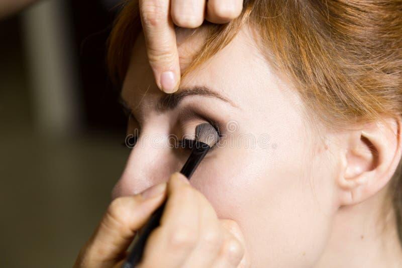 Fermez-vous de la jeune belle jeune mariée appliquant le maquillage par l'artiste de maquillage photos libres de droits
