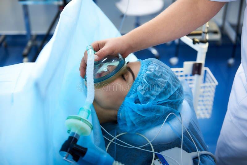 Fermez-vous de la jeune dame obtenant la narcose avant la chirurgie image stock