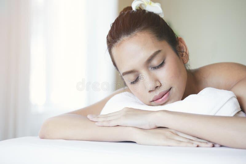 Fermez-vous de la jeune femme asiatique attirante dormant pendant l'obtention du traitement de station thermale photos stock
