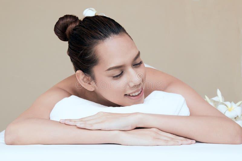 Fermez-vous de la jeune femme asiatique attirante souriant et obtenant la station thermale photographie stock