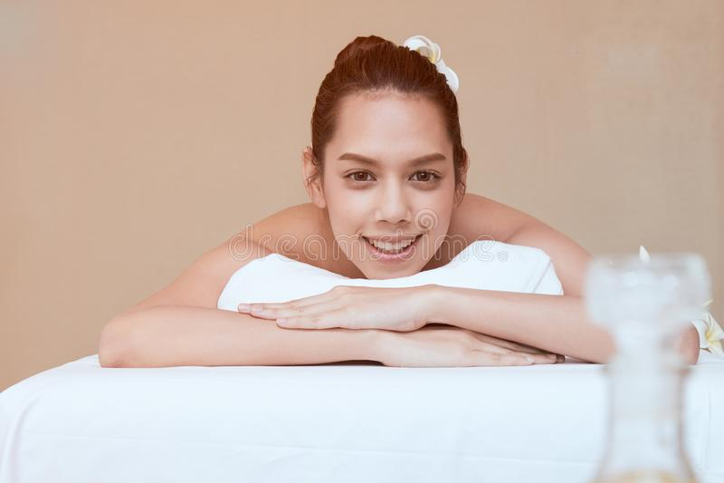 Fermez-vous de la jeune femme asiatique attirante souriant et obtenant la station thermale photo stock