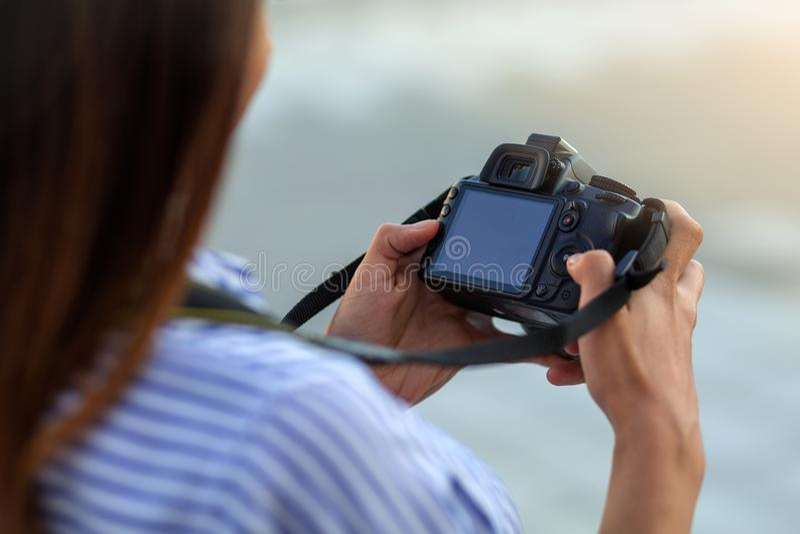 Fermez-vous de la jeune femme avec la caméra regardant l'écran photographie stock