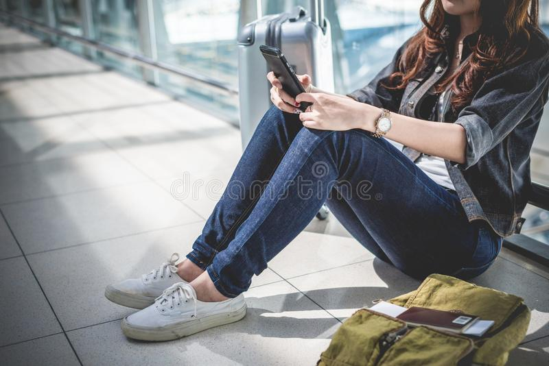 Fermez-vous de la jeune femme avec le d?part de attente de bagage de sac et de valise tout en se reposant dans le salon d'a?ropor photos libres de droits