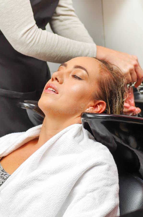 Fermez-vous de la jeune femme heureuse avec la tête de lavage de coiffeur au salon de coiffure, à la beauté et au concept de pers photographie stock libre de droits