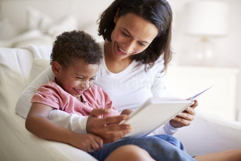 Fermez-vous de la jeune mère adulte d'Afro-américain s'asseyant dans un fauteuil lisant un livre avec son fils de trois ans sur s photos stock