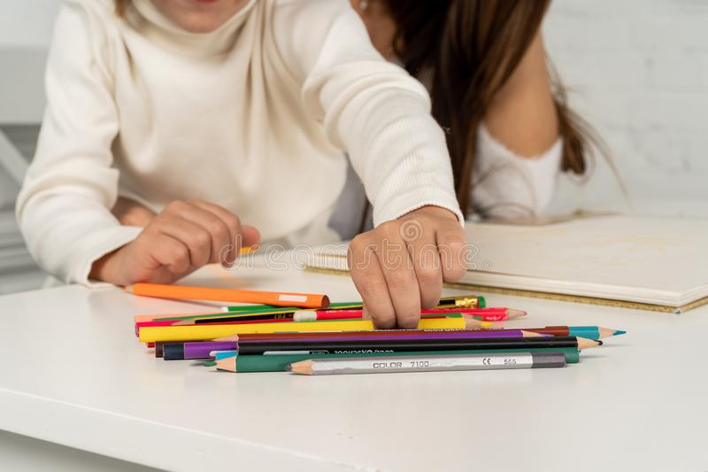 Fermez-vous de la jeune mère heureuse et du petit dessin de fils avec les crayons colorés image stock