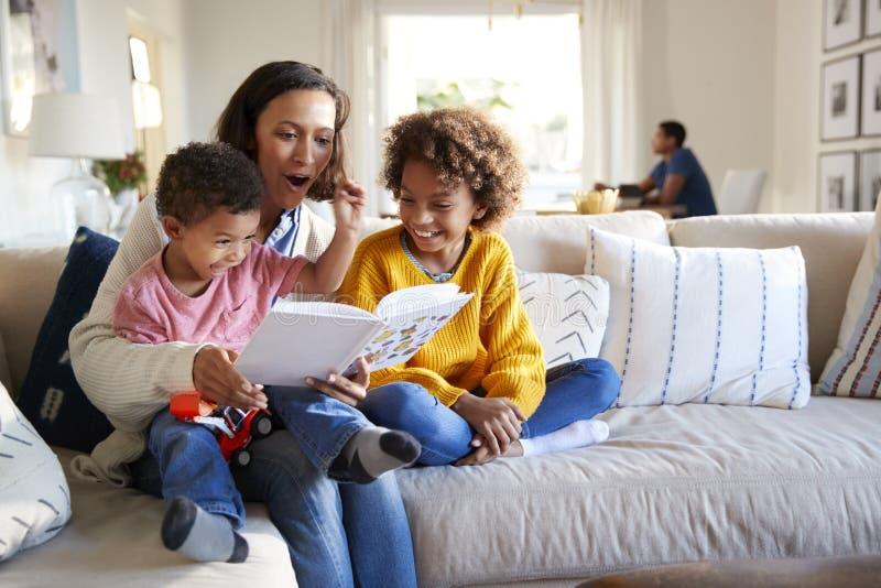 Fermez-vous de la jeune mère s'asseyant sur un sofa dans le salon lisant un livre à ses deux enfants, père s'asseyant à une table photo libre de droits