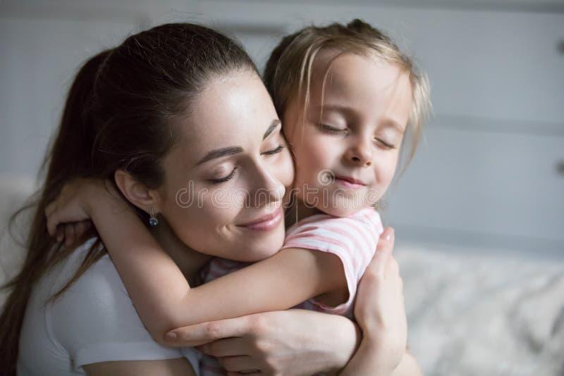 Fermez-vous de la jeune maman étreignant la petite fille mignonne images stock
