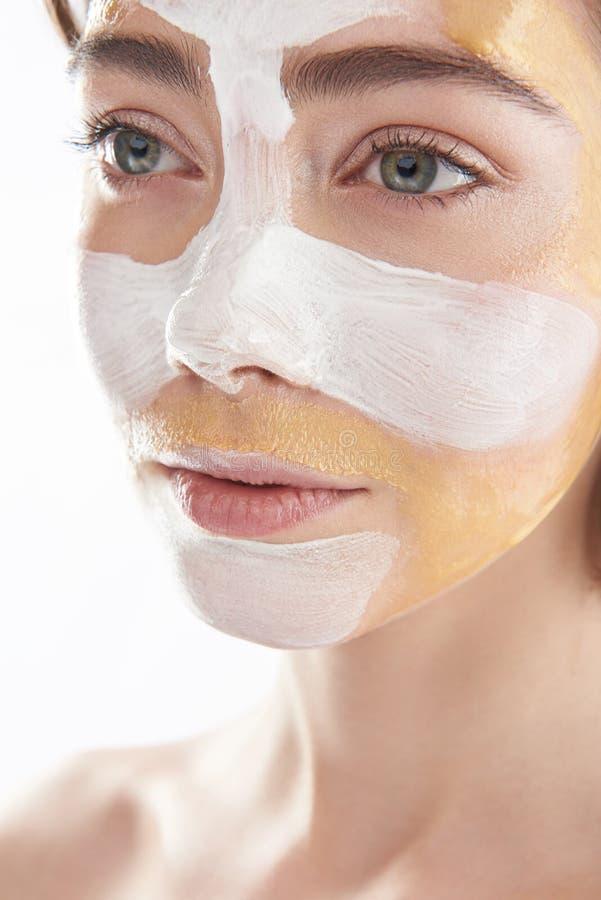 Fermez-vous de la jolie femme avec le masque cosmétique photo stock