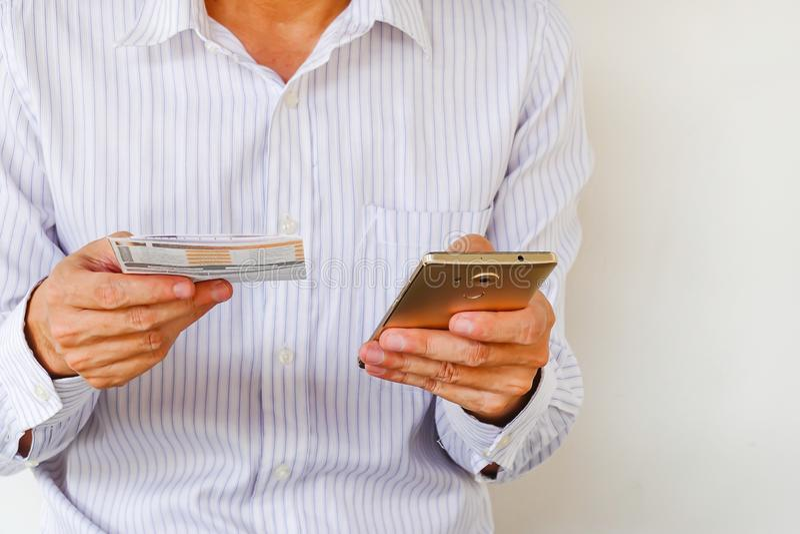 Fermez-vous de la liste de contrôle de l'homme utilisant des opérations bancaires pour la carte de crédit par le téléphone p image libre de droits