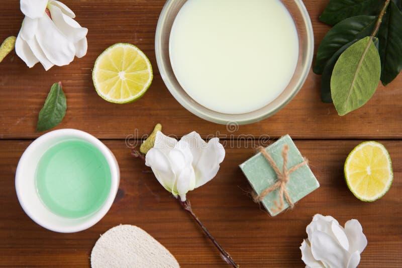 Fermez-vous de la lotion, de la crème et du savon de corps sur le bois image stock