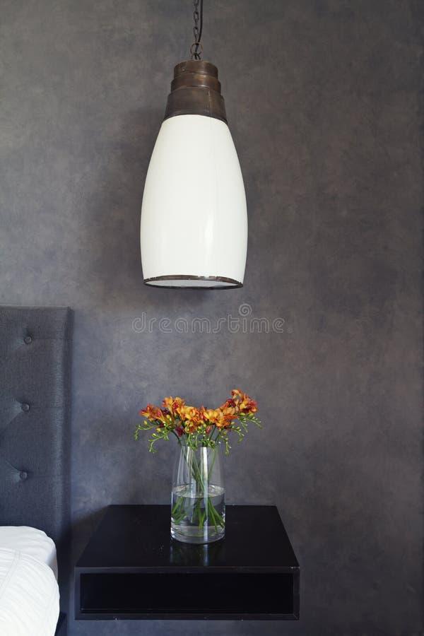 Fermez-vous de la lumière et des fleurs pendantes sur la table de côté de lit image stock