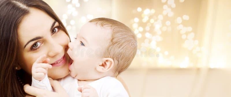 Fermez-vous de la mère avec le bébé au-dessus des lumières de Noël photos stock