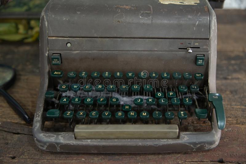 Fermez-vous de la machine à écrire endommagée par vintage sur la table en bois photographie stock
