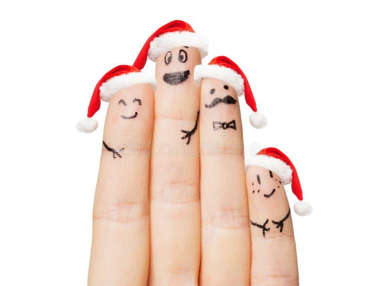 Fermez-vous de la main avec quatre doigts dans des chapeaux de Santa images stock