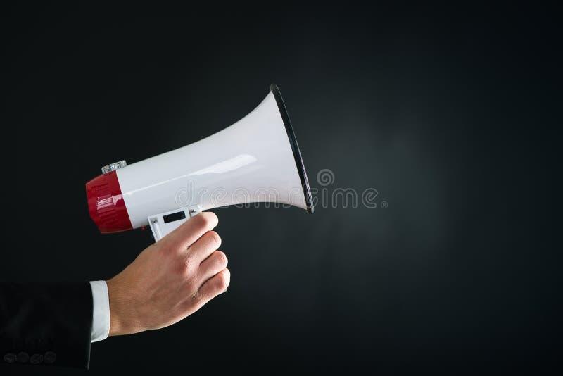 Fermez-vous de la main de businessmans tenant le mégaphone photographie stock libre de droits