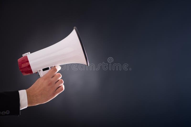 Fermez-vous de la main de businessmans tenant le mégaphone image stock