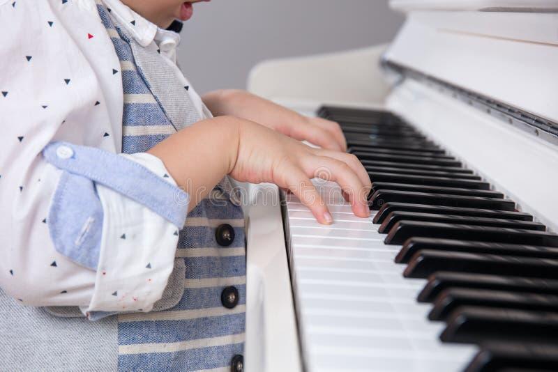 Fermez-vous de la main chinoise asiatique du ` s de petit garçon sur le piano image libre de droits