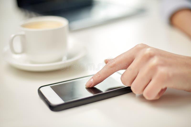 Fermez-vous de la main de femme avec le smartphone et le café photographie stock