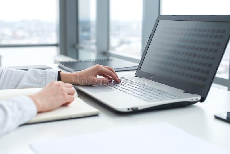 Fermez-vous de la main de femme d'affaires travaillant sur l'ordinateur portable images libres de droits